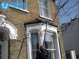 Experienced gutter cleaner in action in London